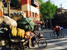 Chinese local cycling with her belongings